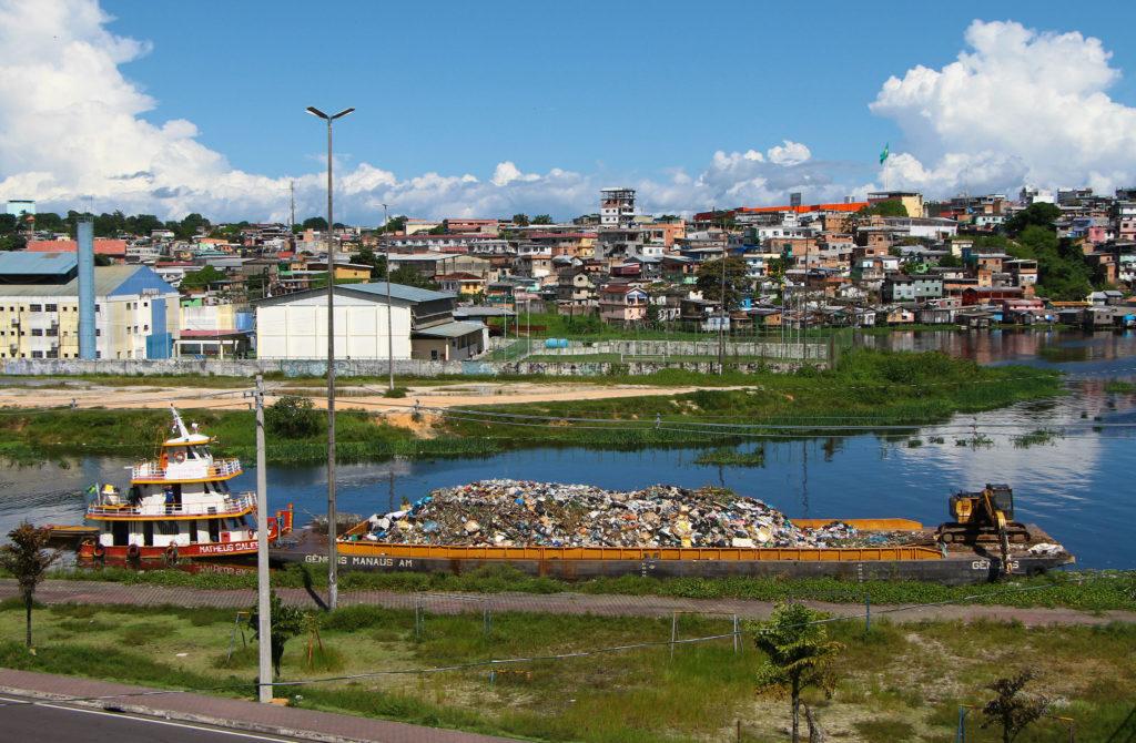 Balsa transporta lixo em rio na cidade de Manaus