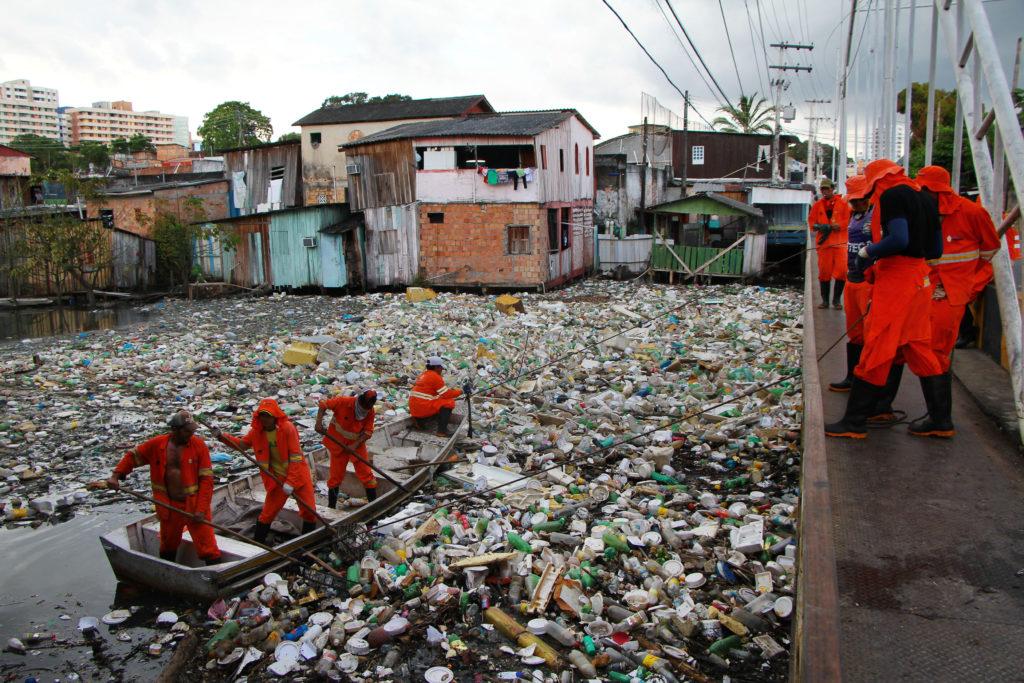 Garis trabalham em limpeza de igarapé repleto de lixo