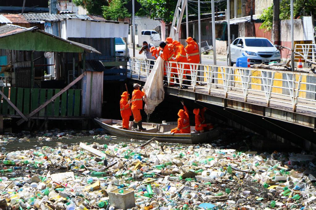 Garis recolhem lixo de igarapé com auxílio de equipes na ponte