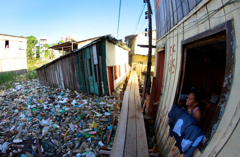 Mulher na janela e criança na passarela de madeira em meio a grande quantidade de lixo em igarapé de Manaus.