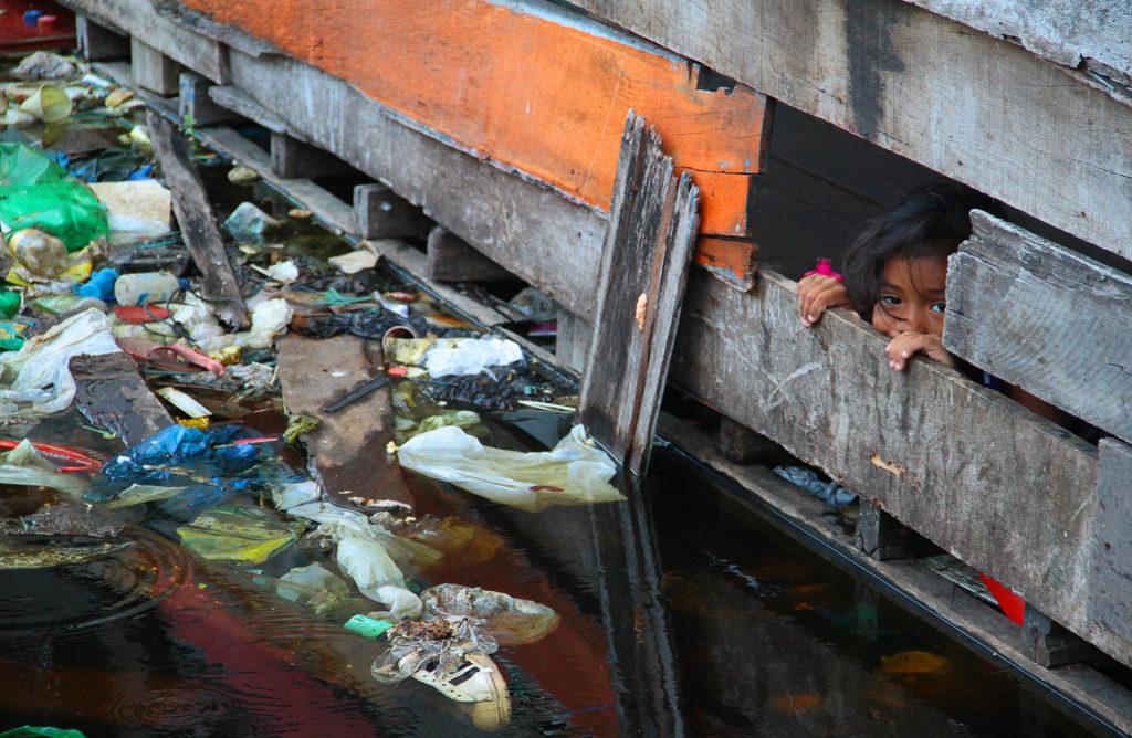 criança observa lixo pela janela de sua casa em Manaus.