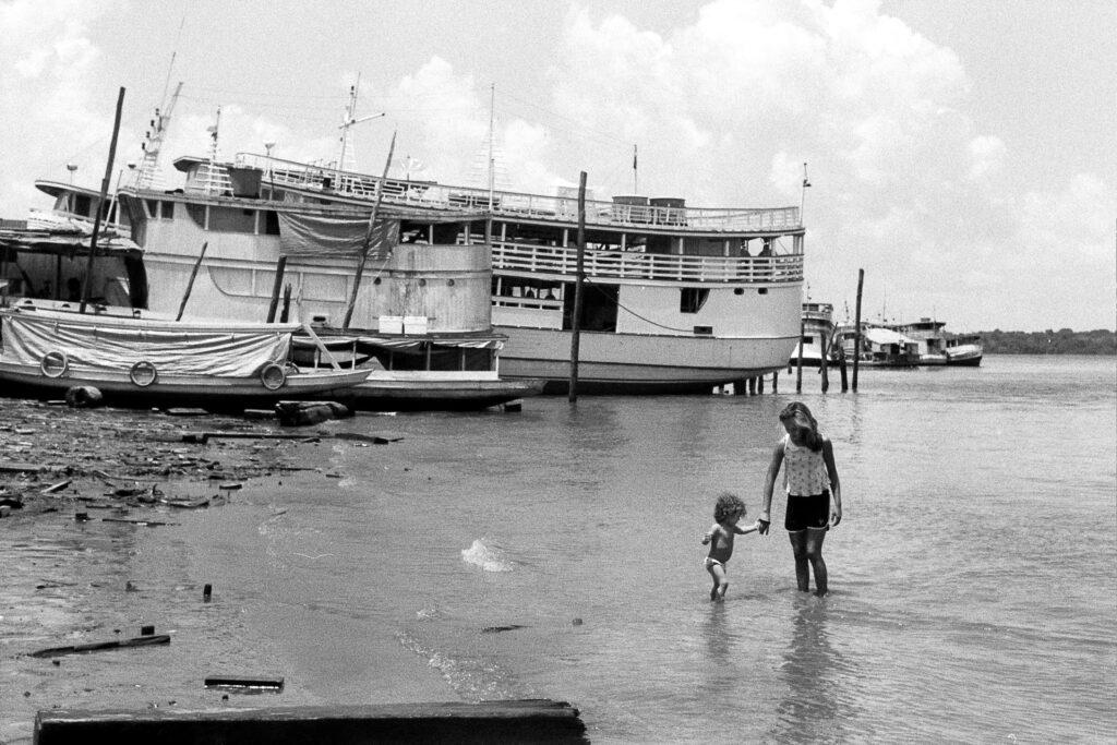 irma leva filho pela mão em margem de rio