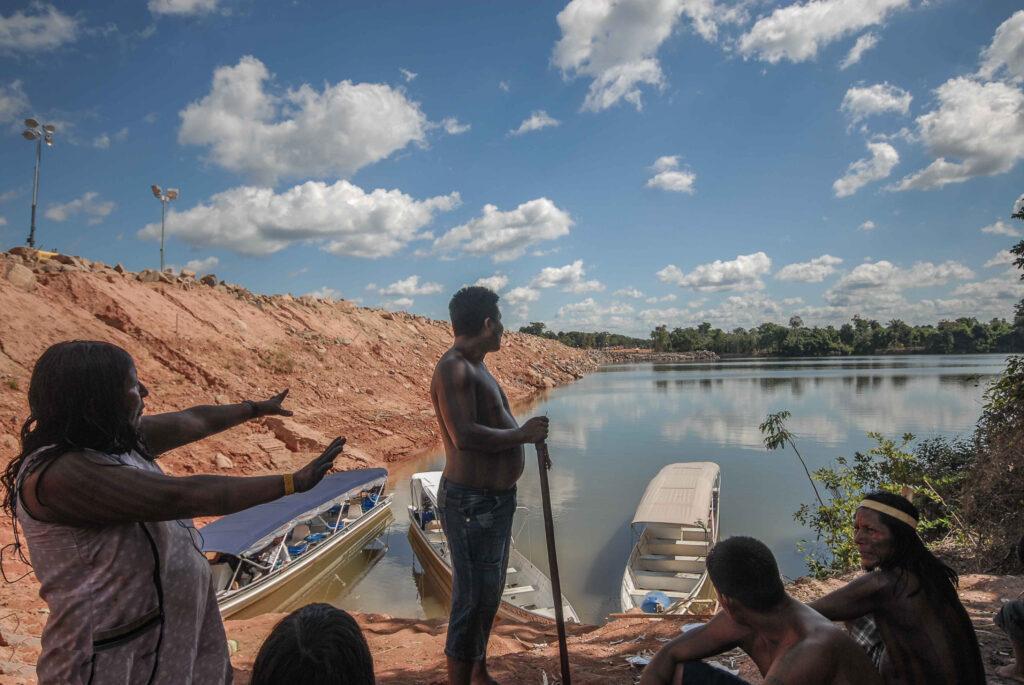Uma mulher indígena estende os braços em direção ao rio. Ao lado, há um banco de terra vermelha. Outros indígenas estão ao redor da mulher.