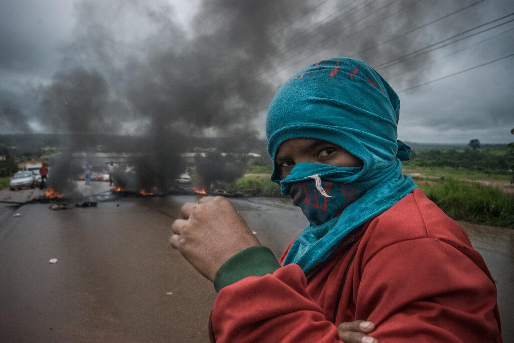 Um manifestante usa uma camiseta azul como máscara, tampando todo seu rosto. Atrás dele, pneus queimam.