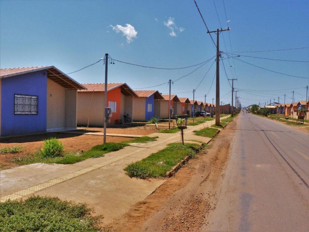 Foto de um conjunto de casas iguais roxas e laranjas. As casas se estendem por toda rua.