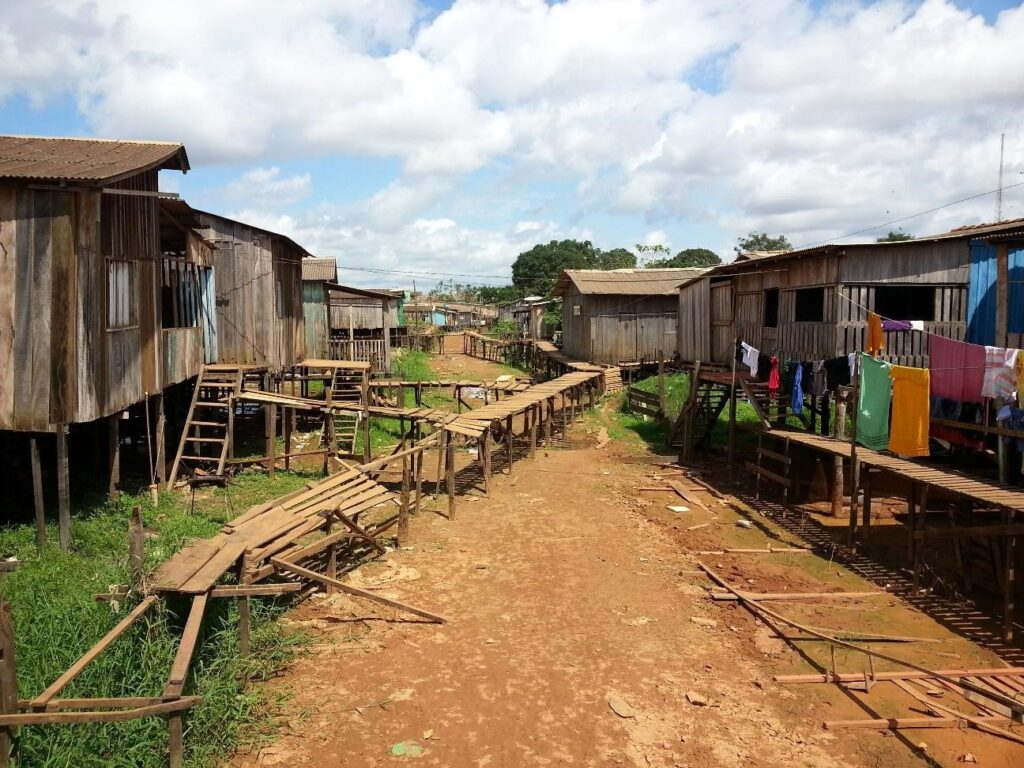Foto de casas de palafitas. Do lado esquerdo e direito, casa marrons empobrecidas. No centro, terra batida e uma ponte de madeira quebrada.