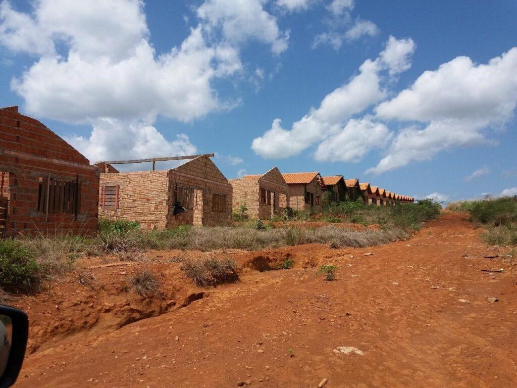 Foto de casas abandonadas em uma estrada sem terra. Algumas construções não apresentam teto.