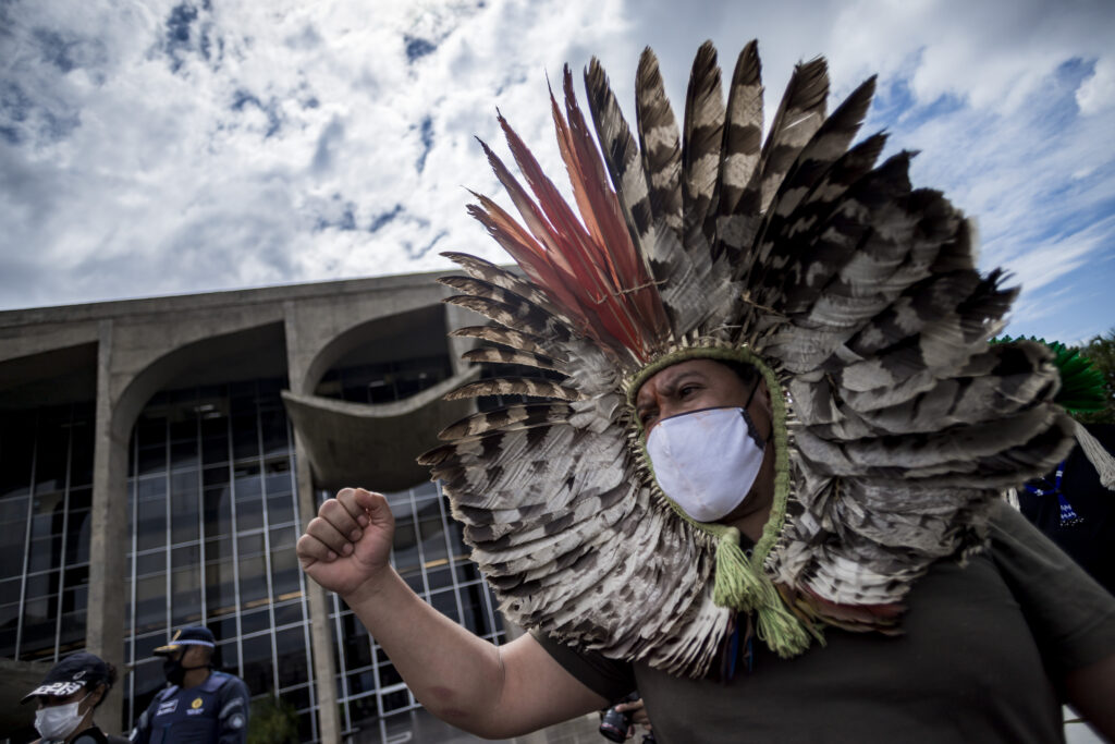 Homem indígena usando um cocar que emoldura seu rosto, com o punho cerrado.