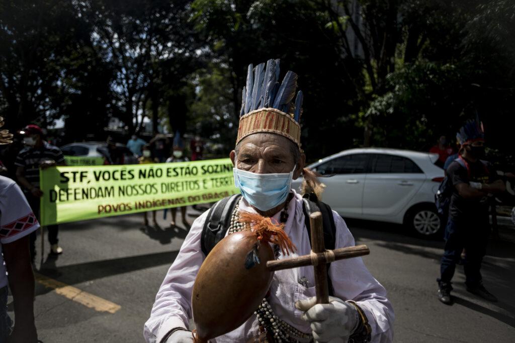 Indígena segura uma cruz e um instrumento, usando um cocar e uma máscara. Ao fundo, lê-se: STF defendam nossos direitos