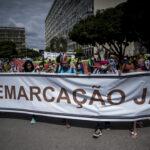 indígenas seguram cartaz escrito Demarcação Já
