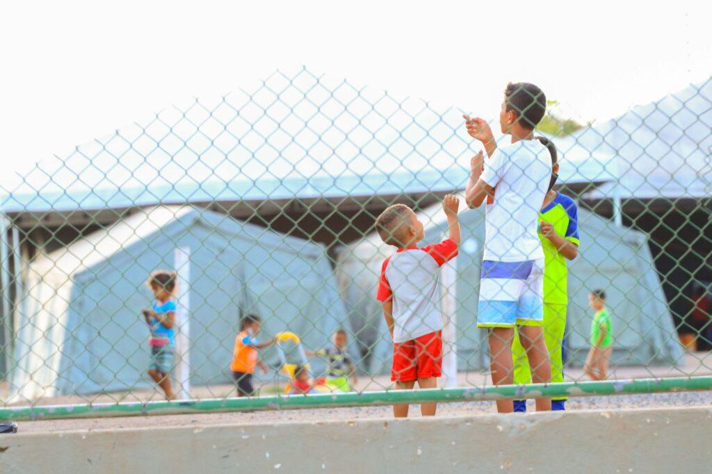 Crianças soltam pipa dentro da ocupação cercada por arames.