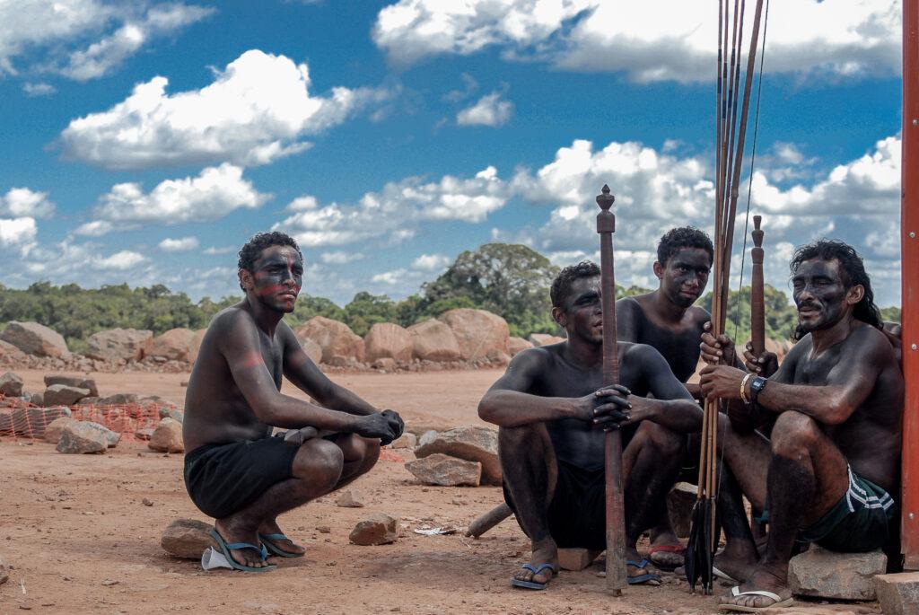 Grupo de indígenas pintados de tinta preta e vermelha sentados segurando flechas.
