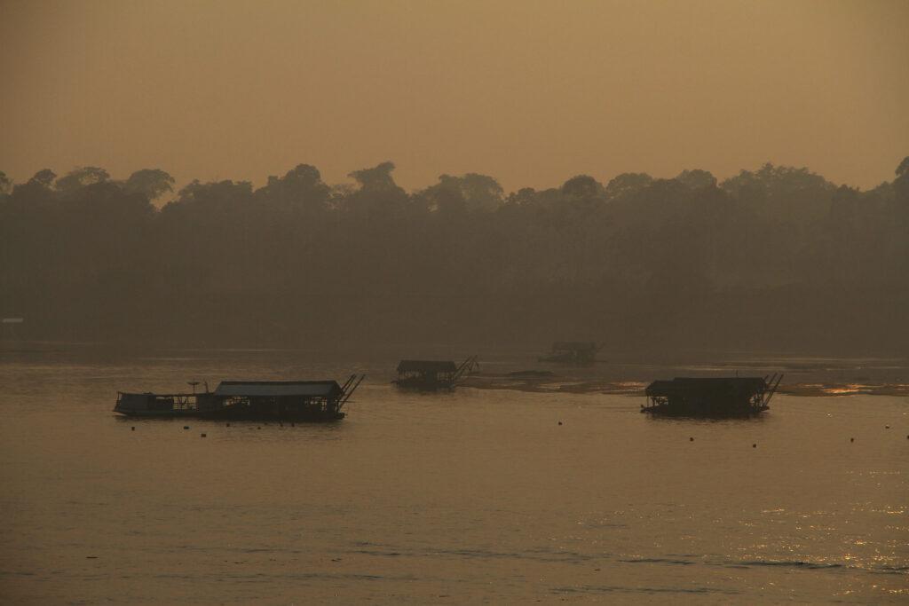 embarcações em um rio. Fumaça embaça a vista. O fundo está amarelado pelo incêndio