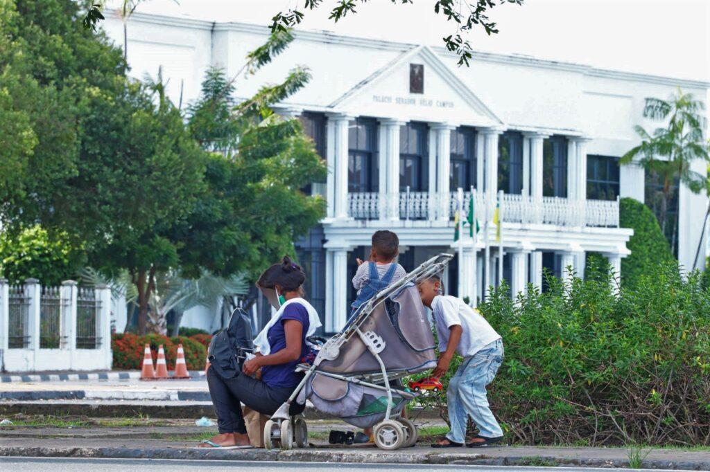 uma mulher sentada na calçada ao lado de suas crianças e um carrinho de bebê