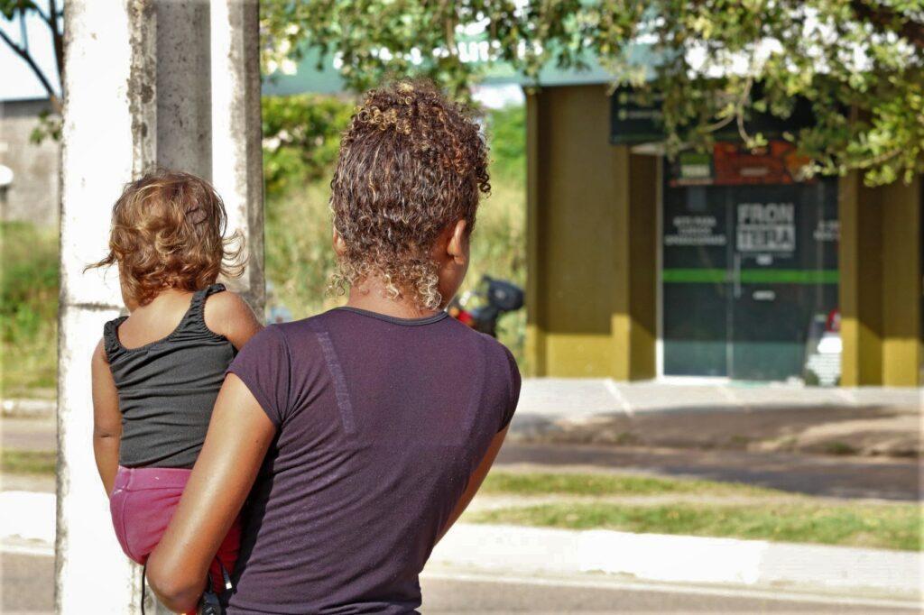 Uma mulher negra segura sua filha no colo. Ambas estão de costas