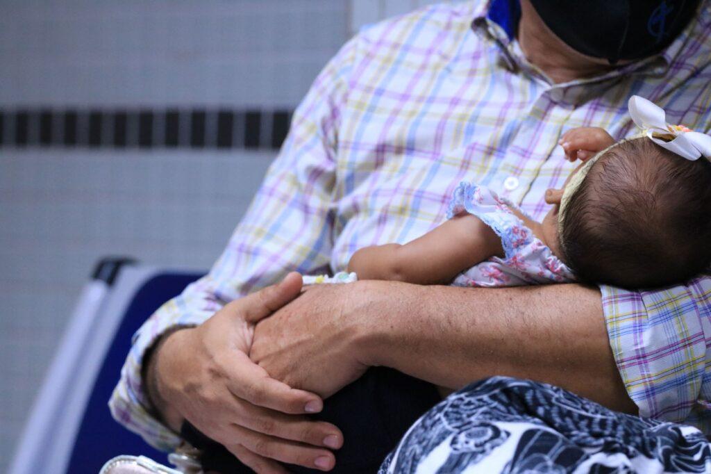 Homem segura um bebê nos braços