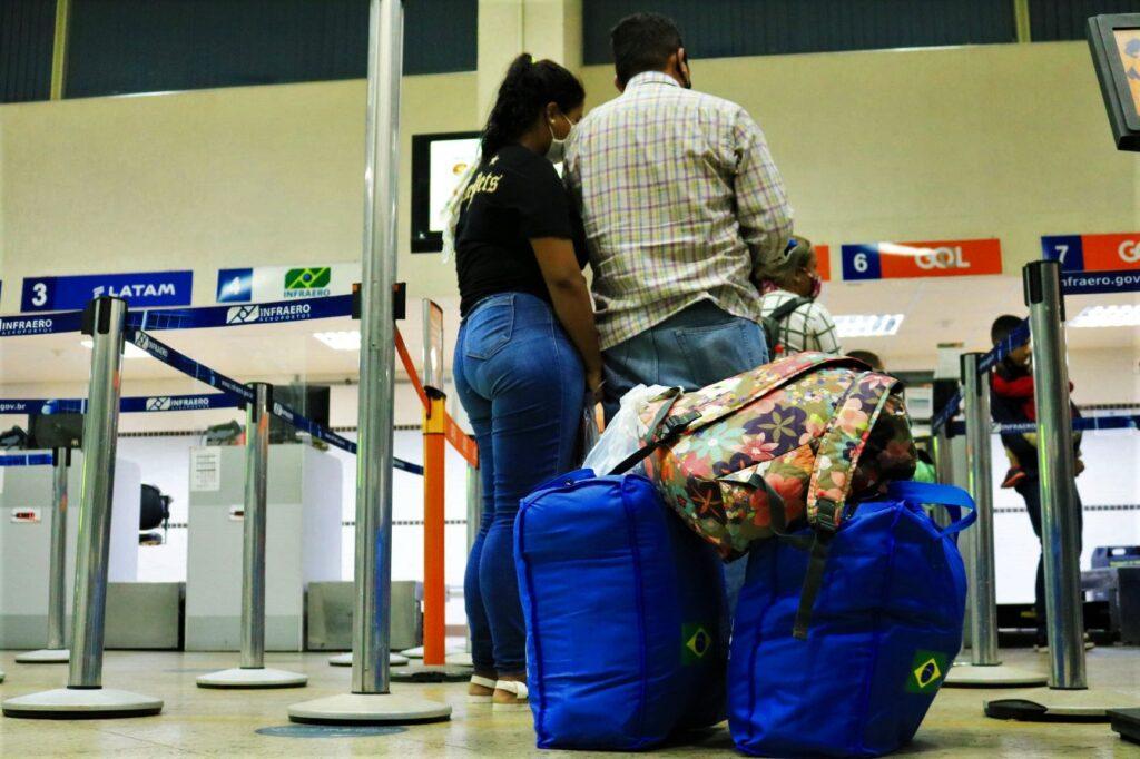 Uma mulher encosta a cabeça no ombro de um homem na fila de espera em um aeroporto.