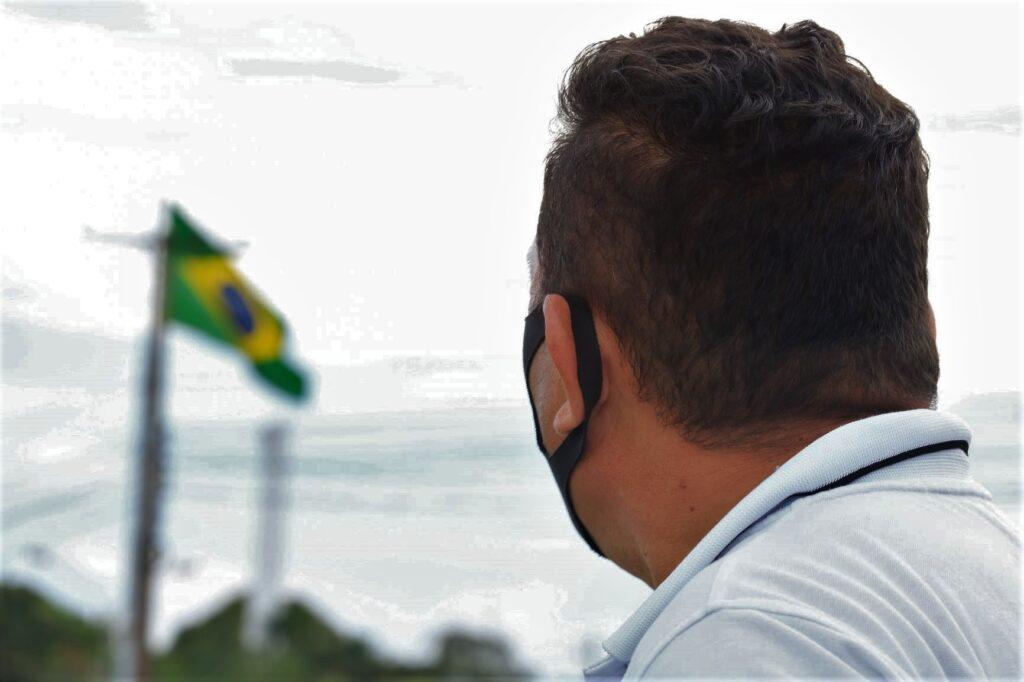 Homem de costas, com uma máscara preta no rosto, olhando para uma bandeira do Brasil.