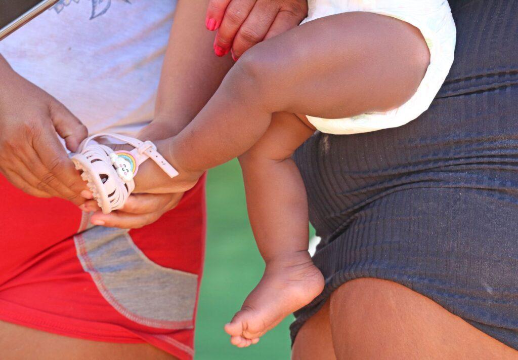 Mãe coloca uma sapatilha nos pés de seu bebê