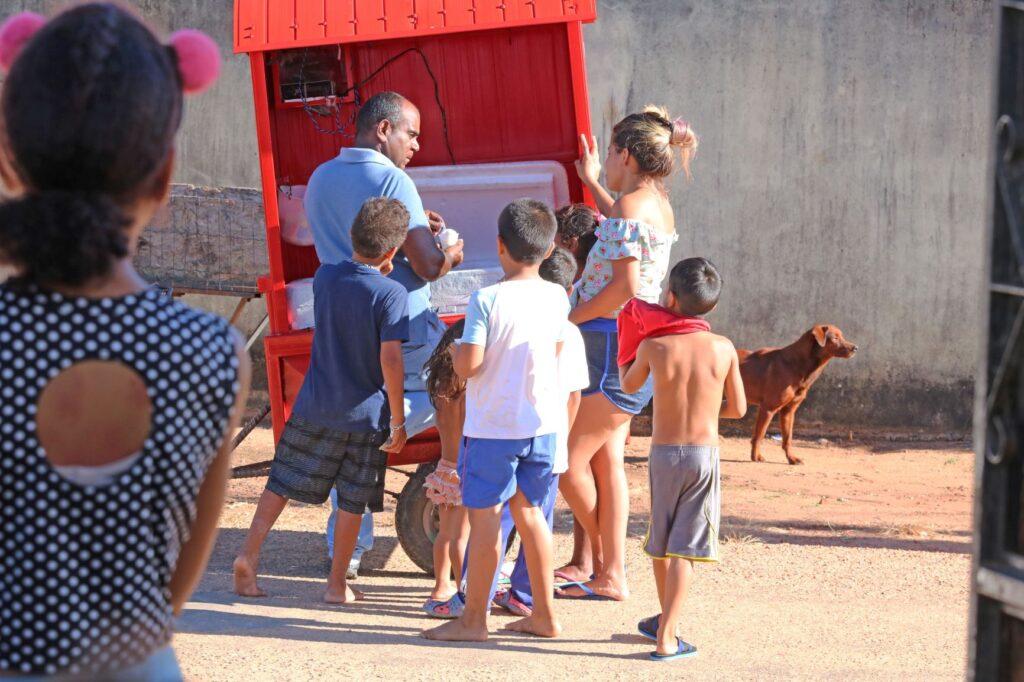 Crianças se amontoam junto de um vendedor de sorvete em um carrinho vermelho.
