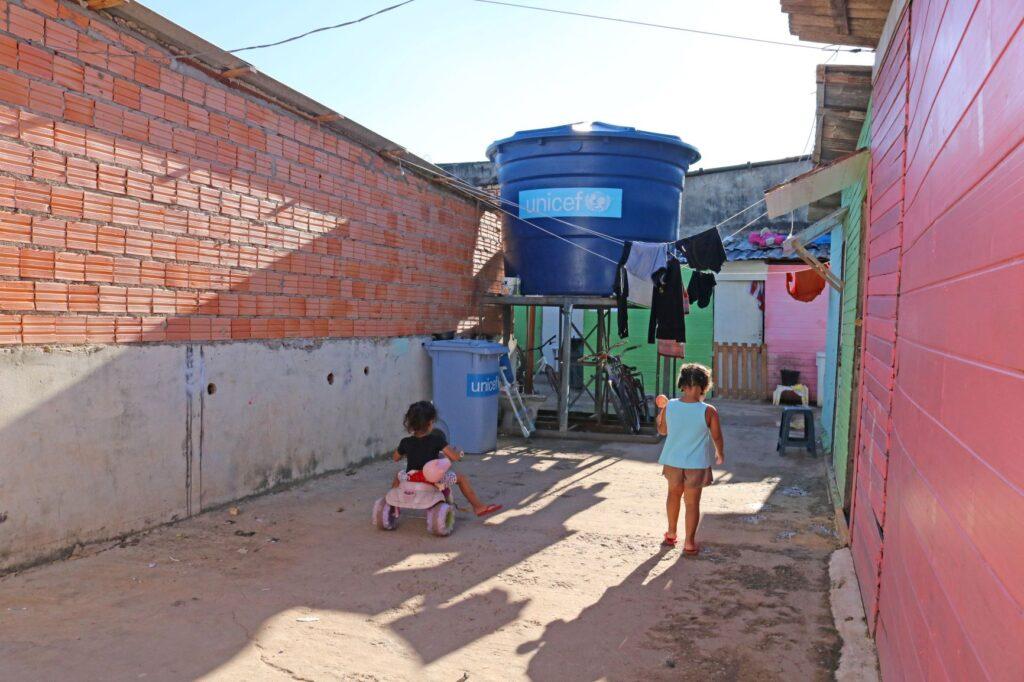 Duas crianças brincam em uma área com construções de tijolos expostos