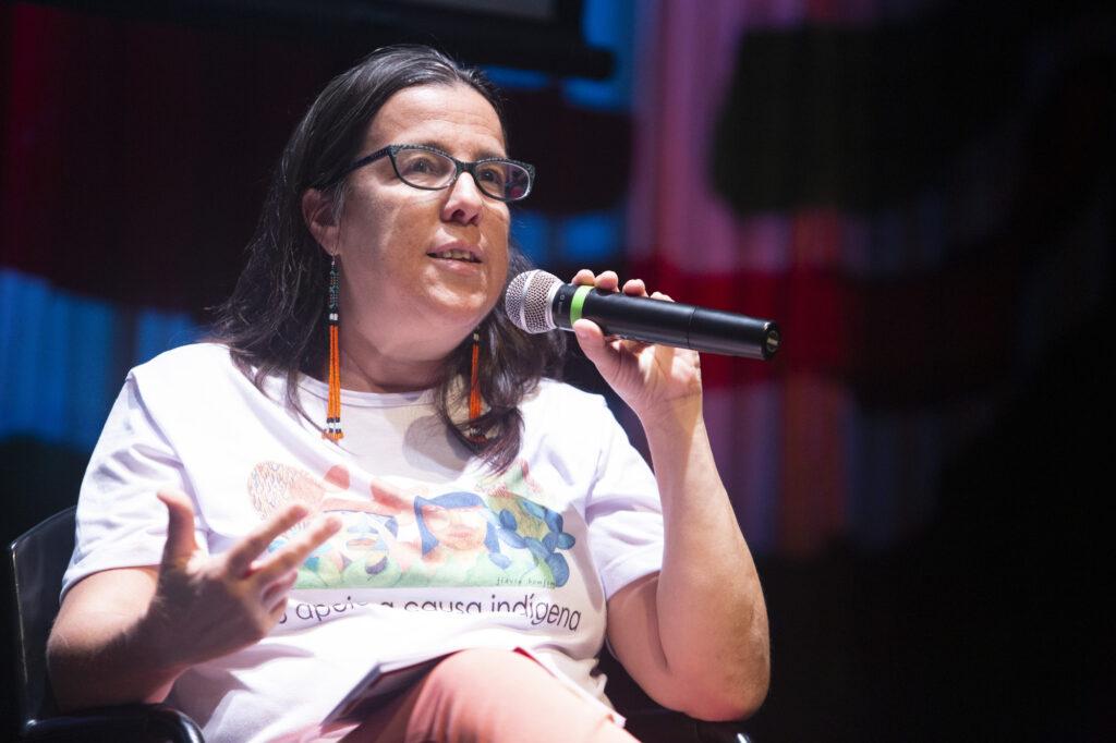 Adriana Ramos sentada com um microfone nas mãos. Ela usa óculos e tem cabelos longos e pretos.