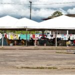 Foto de diversas barracas colocadas sob um barracão