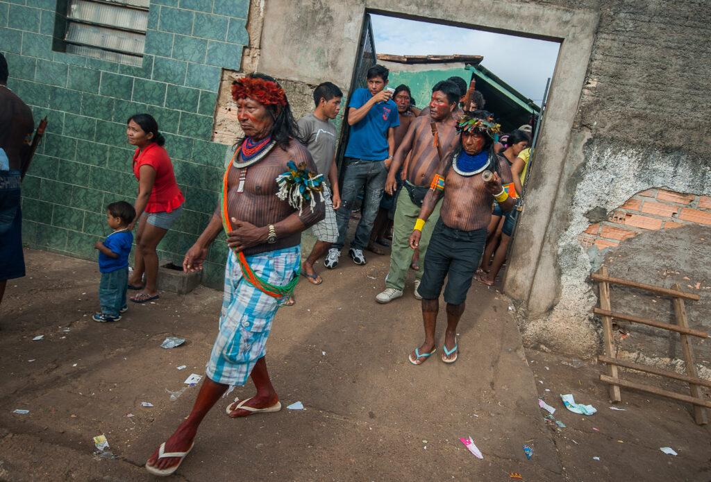 Grupo de indígenas em uma construção. Eles vestem cocar e outros apetrechos