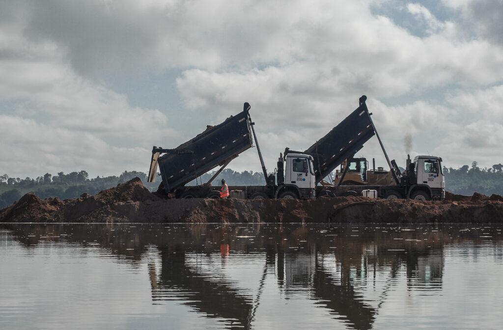 Caminhões com caçambas levantadas na beira de um rio.