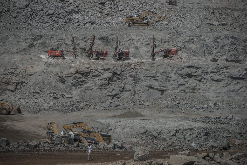 Diversas escavadeiras parecem pequenas na escala do gigante canteiro de obras.