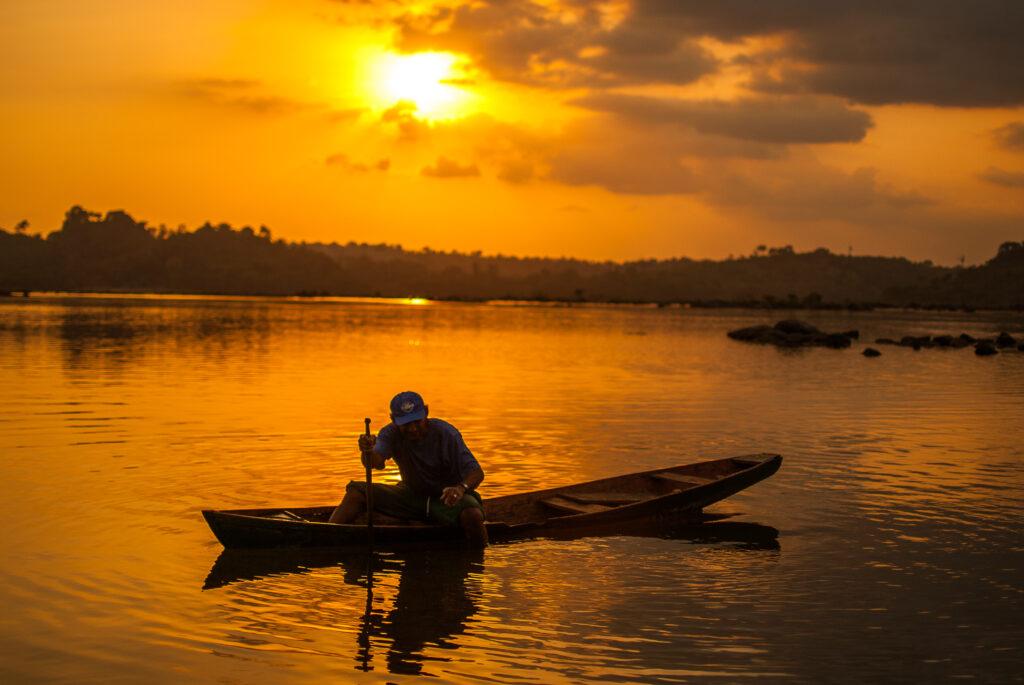 Uma canoa no Xingu. Ao fundo, o por do sol que deixa a paisagem dourada