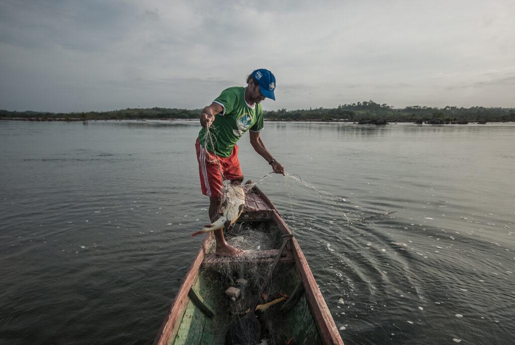 Um homem segura um peixe em uma rede, de pé em uma canoa.