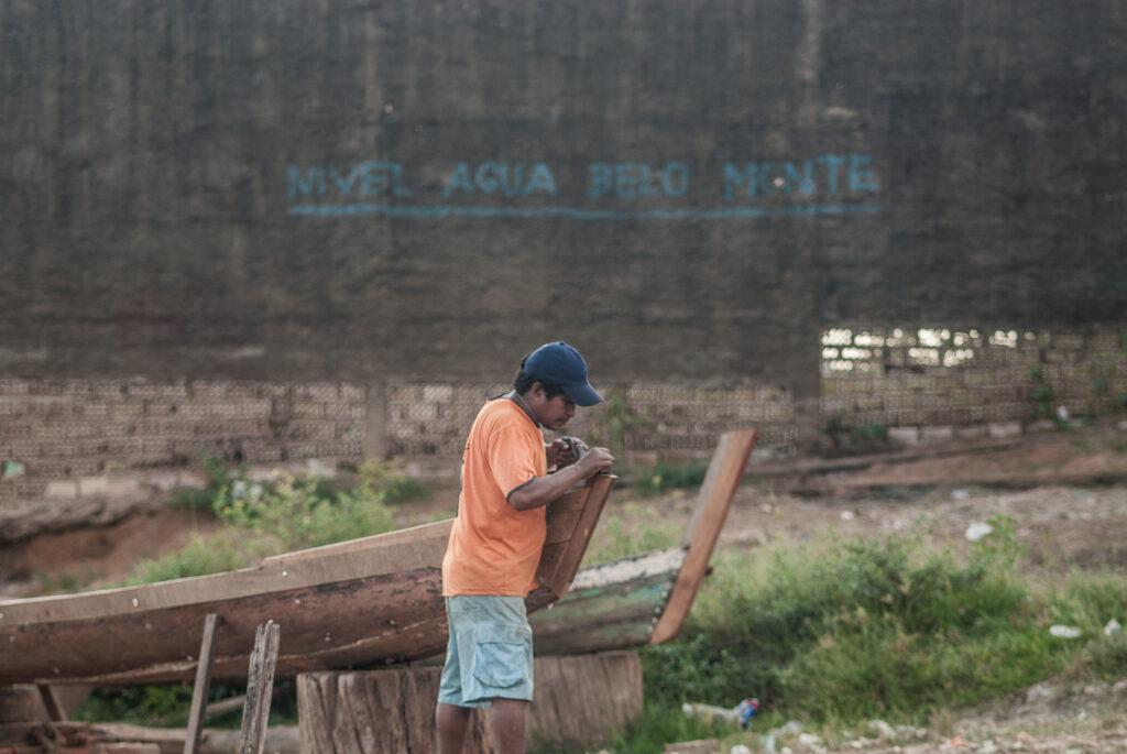 """Um homem ao lado de uma canoa na terra firme. Ao fundo, está escrito """"Nível Água Belo Monte"""""""