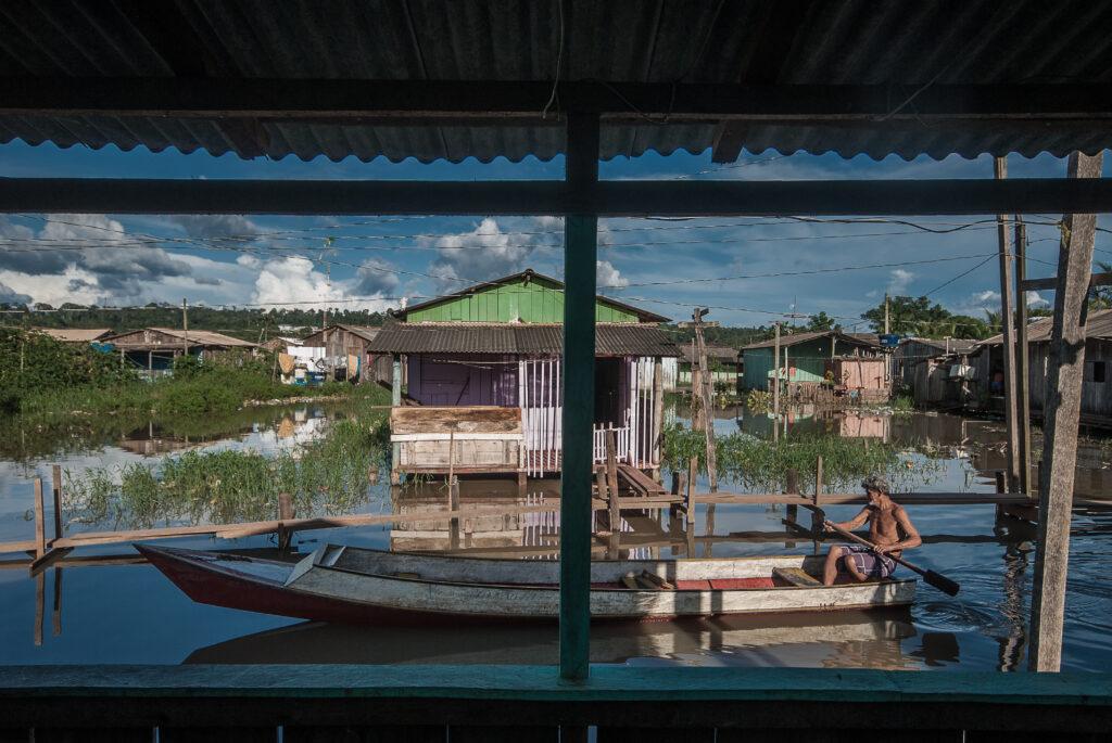 Vista de uma janela para uma rua feita de rio, com uma canoa atravessando