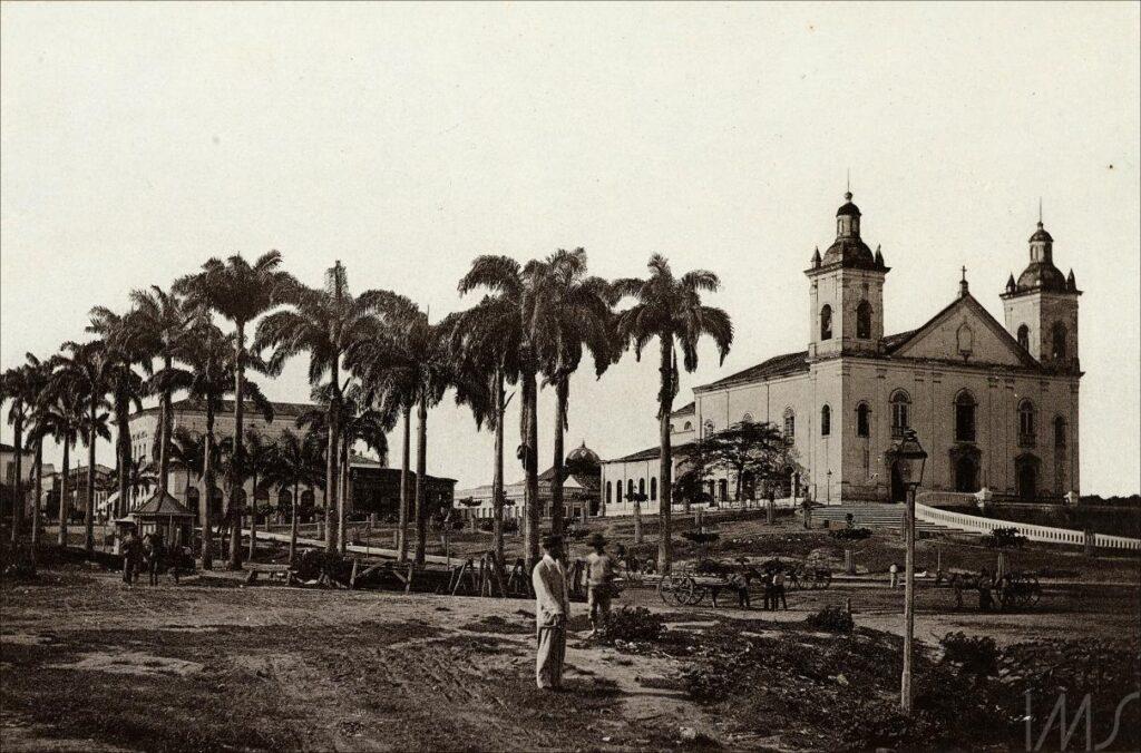 Foto em preto e branco de uma Igreja no horizonte, cercada por palmeiras.