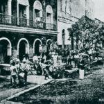 Foto em preto e branco das ruas de Manaus. Grupos de pessoas se reúne em mesas na calçada.
